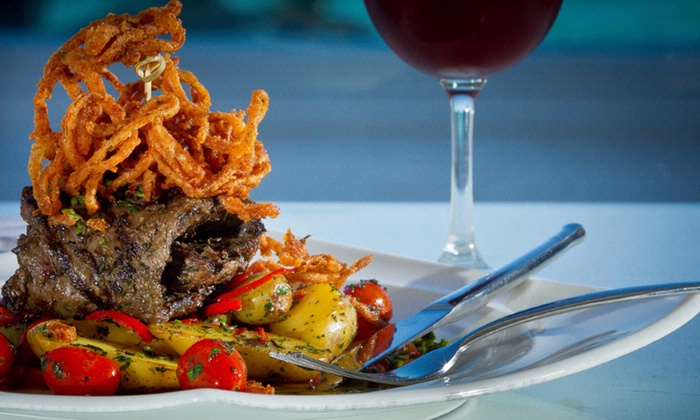 Perfectly grilled steak with crispy string fries and colorful vegetables paired with a glass of red wine.