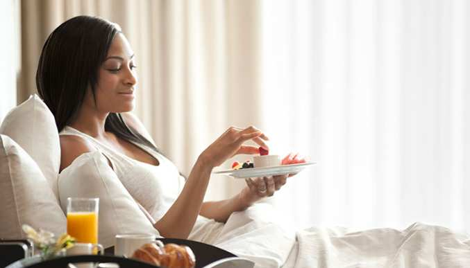Woman enjoys finger food while laying on a bed.