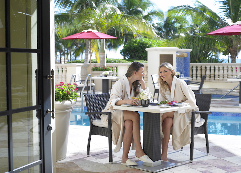 two women in bathrobes enjoying breakfast on the patio at Acqualina.