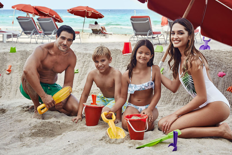 Young family of four on the beach playing in the sand and smiling.