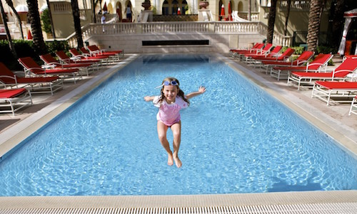 A photo of a young girl jumping into the pool at the Acqualina Resort & Spa on the Beach.