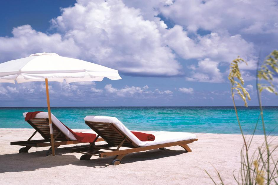 Two empty lounge chairs and beach umbrella facing the ocean.