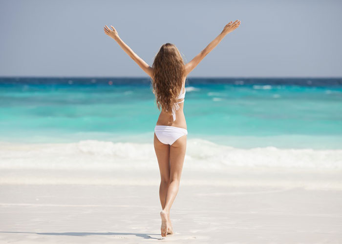 Woman in a bikini with her arms upraised facing the ocean
