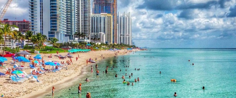 Photo of visitors and residents enjoying the Sunny Isles Beach ocean.