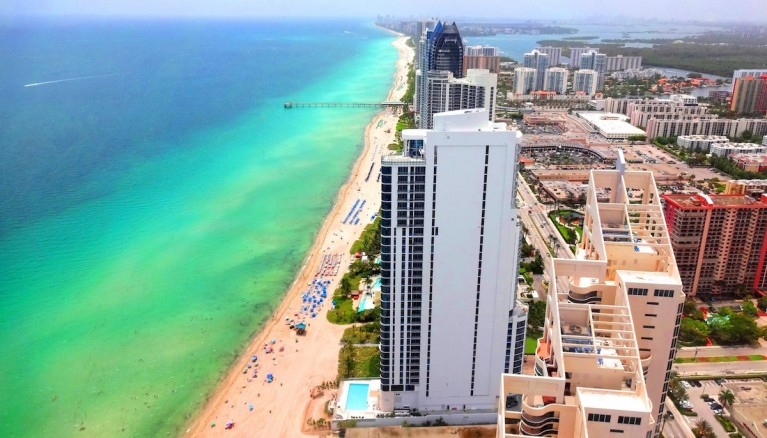 Aerial view of Sunny Isles Beach coastline with Aqua-Green ocean waters.