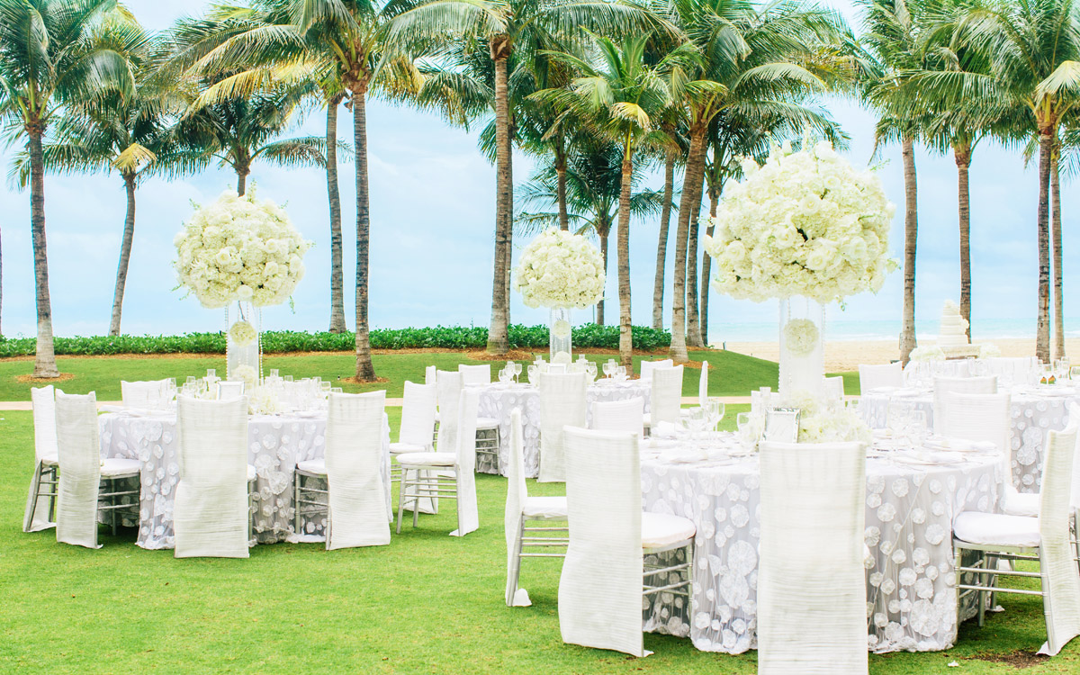 Opulent wedding table settings outdoor on a green lawn in front of palm trees and the beach