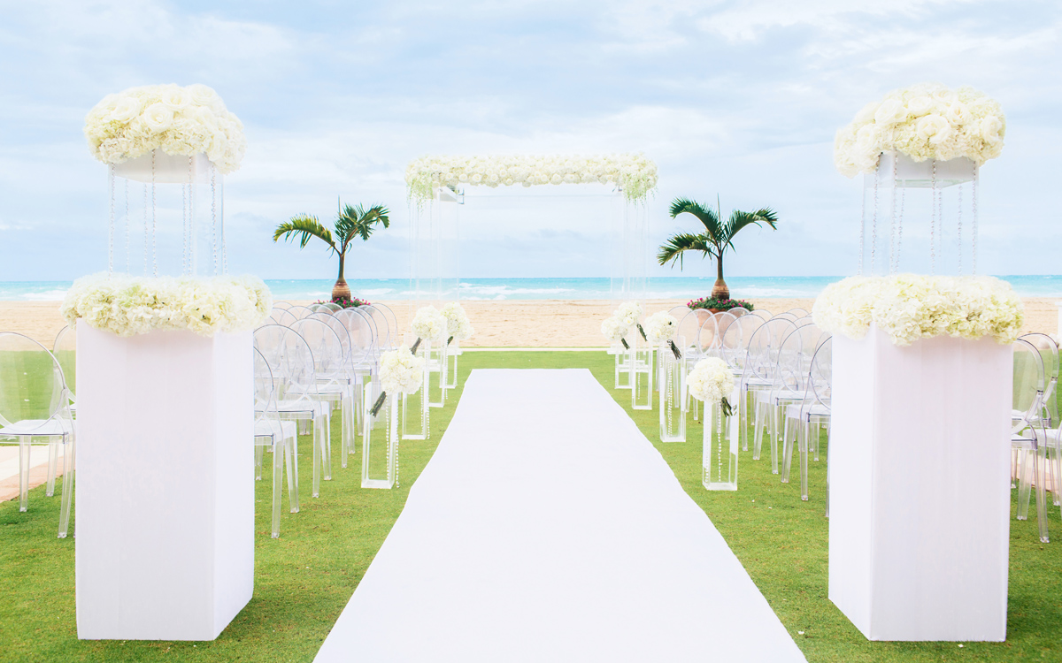 Wedding ceremony setting with all white chairs and arch facing the beach.