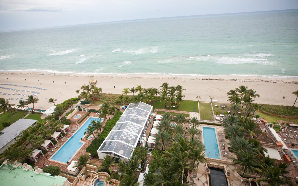 Aerial view of Acqualina Resort's lawn and event space next to the Atlantic ocean coast.