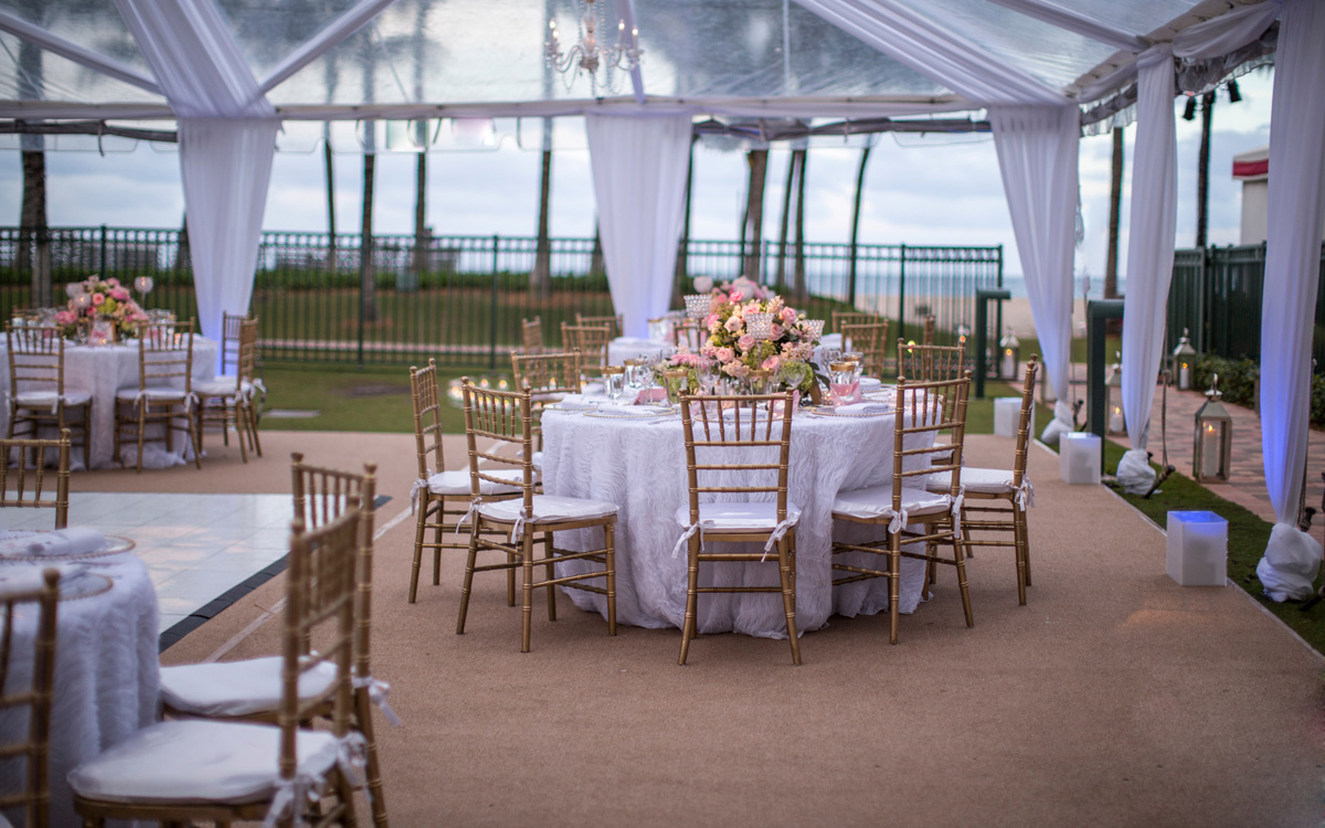 Beautiful tent with tables set up for a party on the lawn at Acqualina