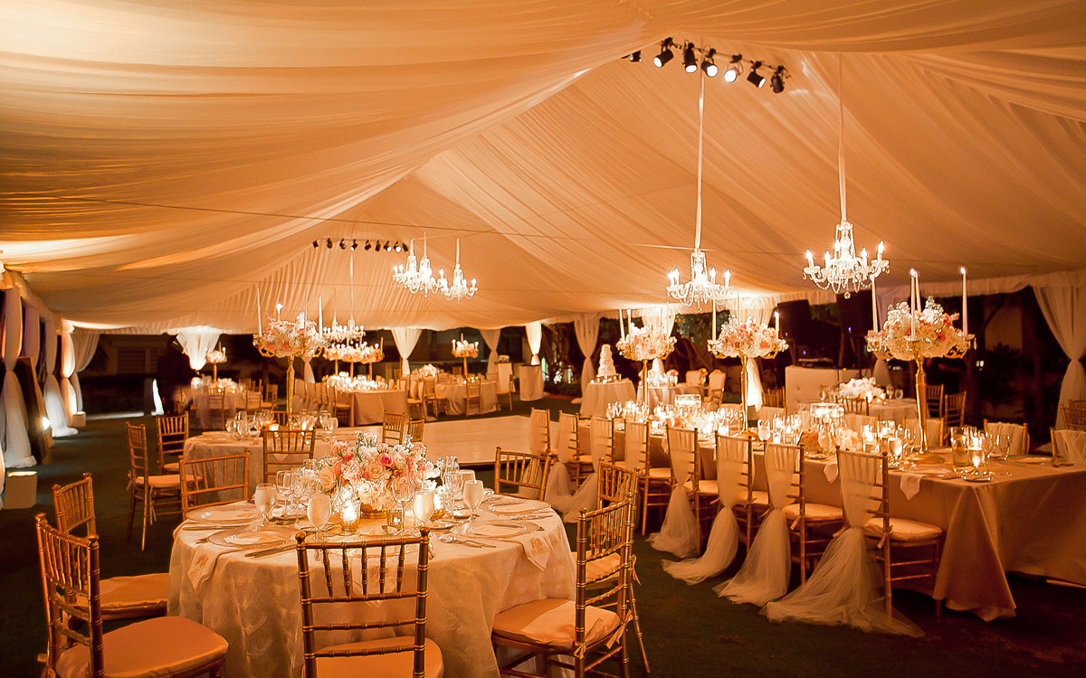 Tent set up in the evening with chandelier light and table settings for a party.