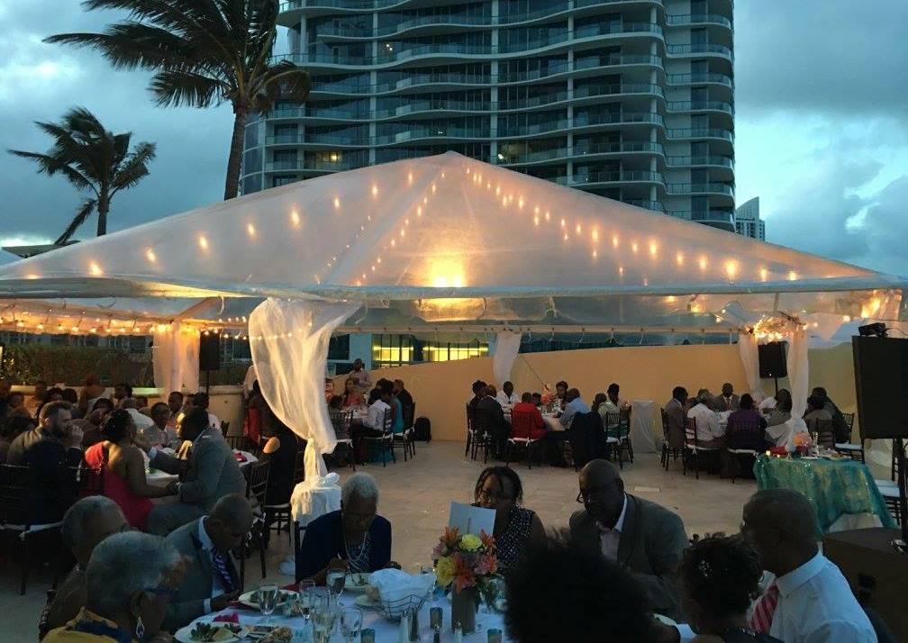 People gathered for a reception outdoor sitting at tables with a tent and lights overhead.