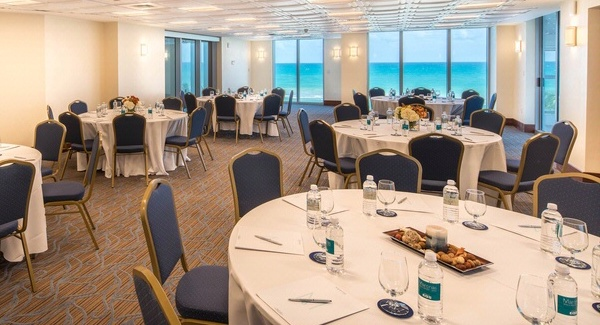 Meeting room with tables and settings with an ocean view.