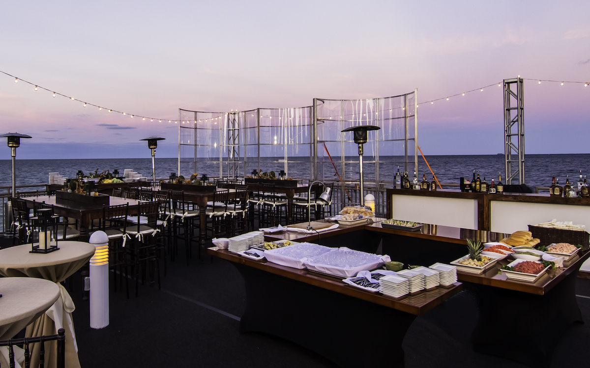 Outdoor reception area with food set up and tables and chairs overlooking the ocean.