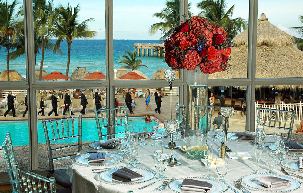 Table setting with flowers in the middle overlooking the Newport pool with wedding party lining up for pictures.
