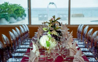 Table setting with a window in the background overlooking the ocean.