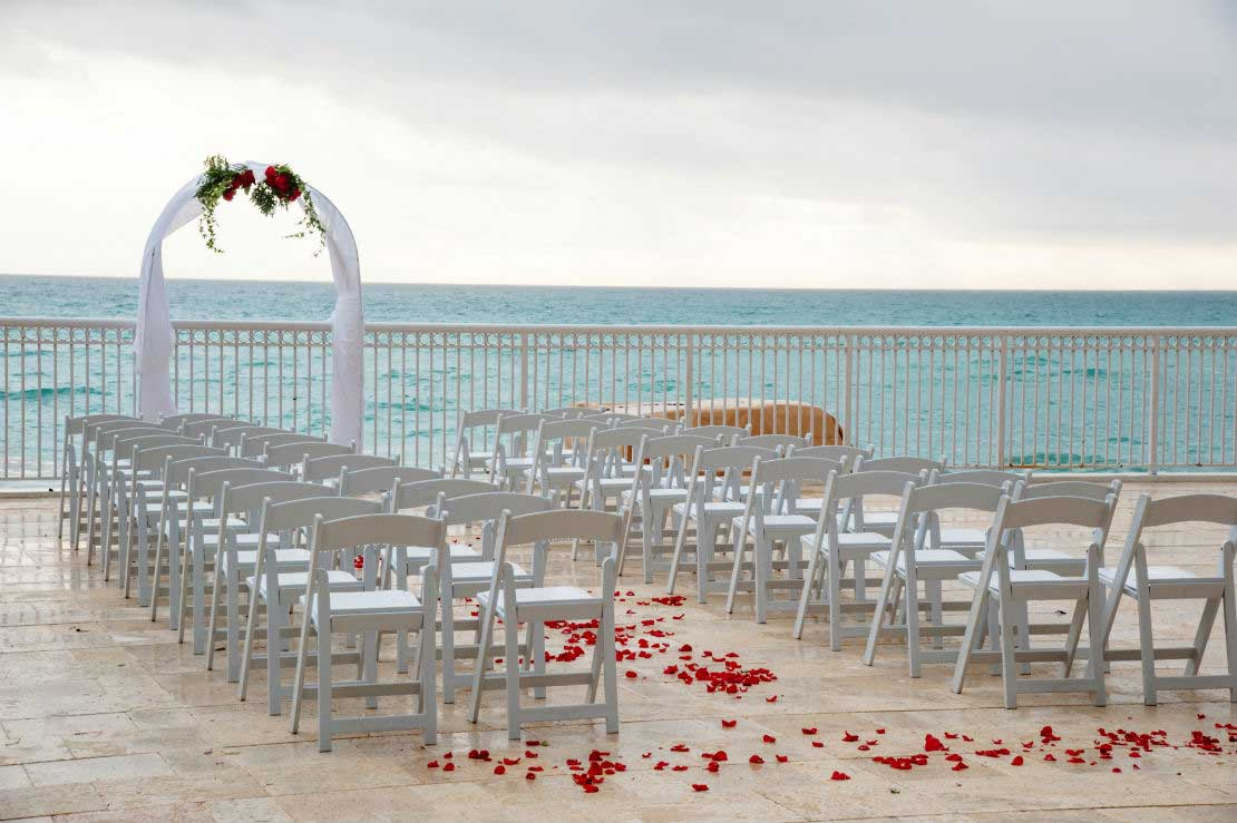 Outdoor wedding with chairs and a arch set up facing the ocean.