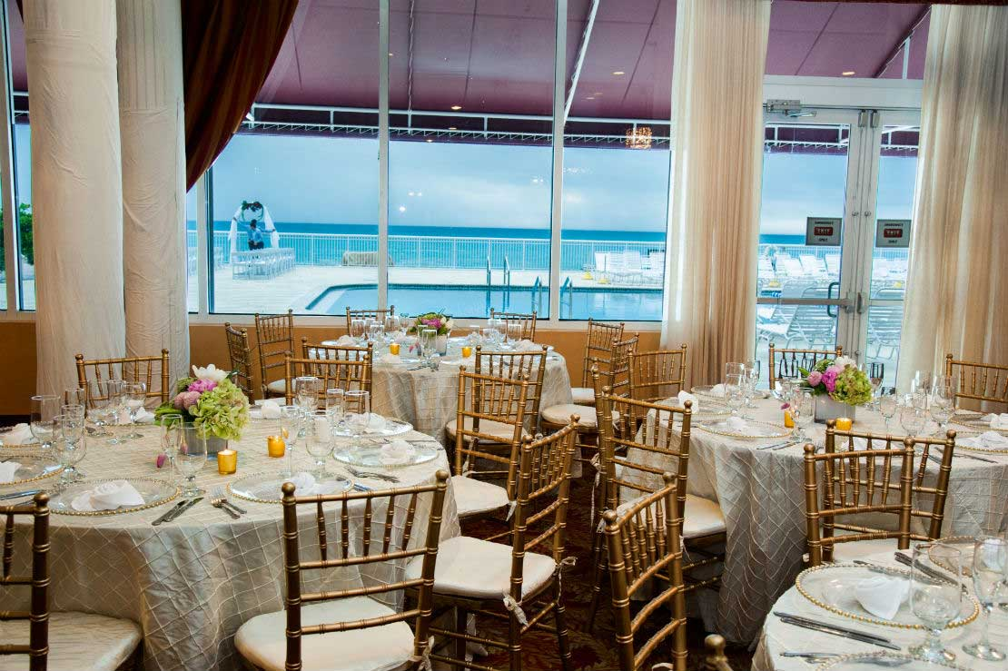 Tables set up in a reception room overlooking the pool and ocean.