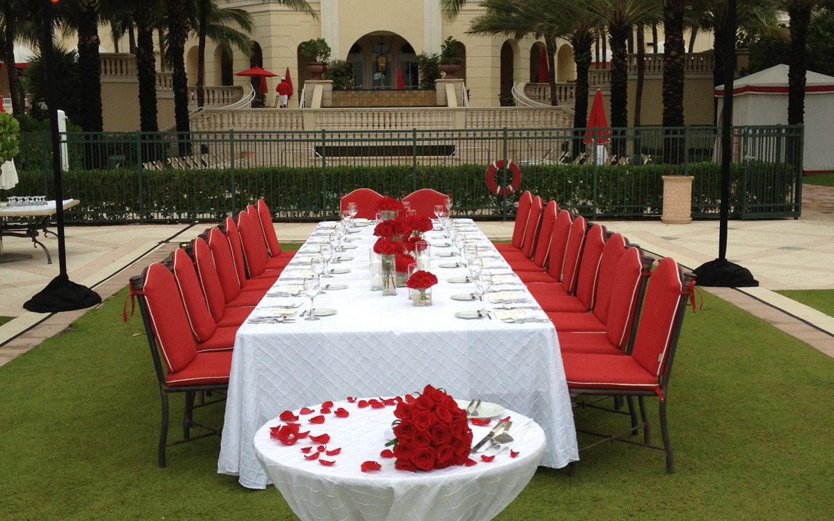 Table set up with rose petals and red chairs in front of opulent lawn setting.
