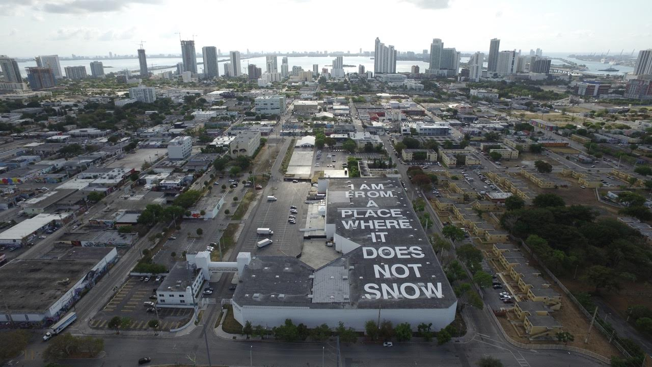 Aerial shot of downtown Miami with writing on top of a building.