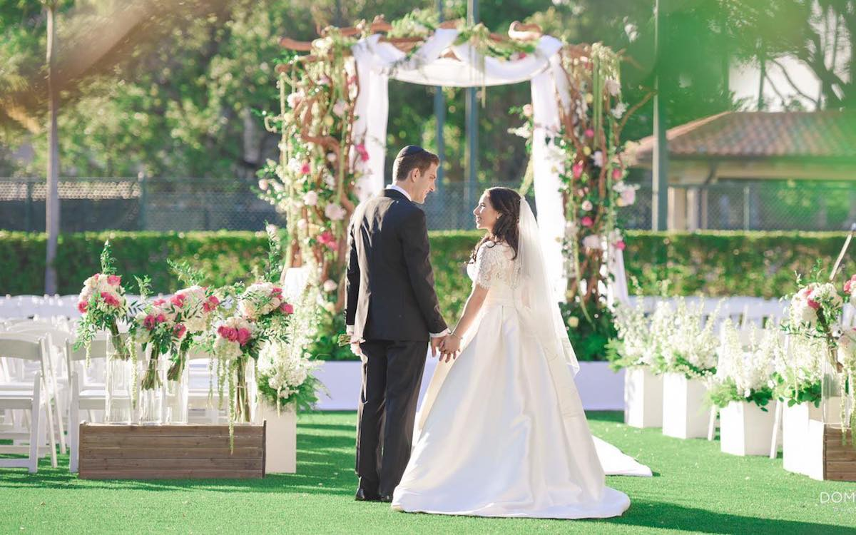 Couple holding hands at Wedding setting at Turnberry Isle Miami