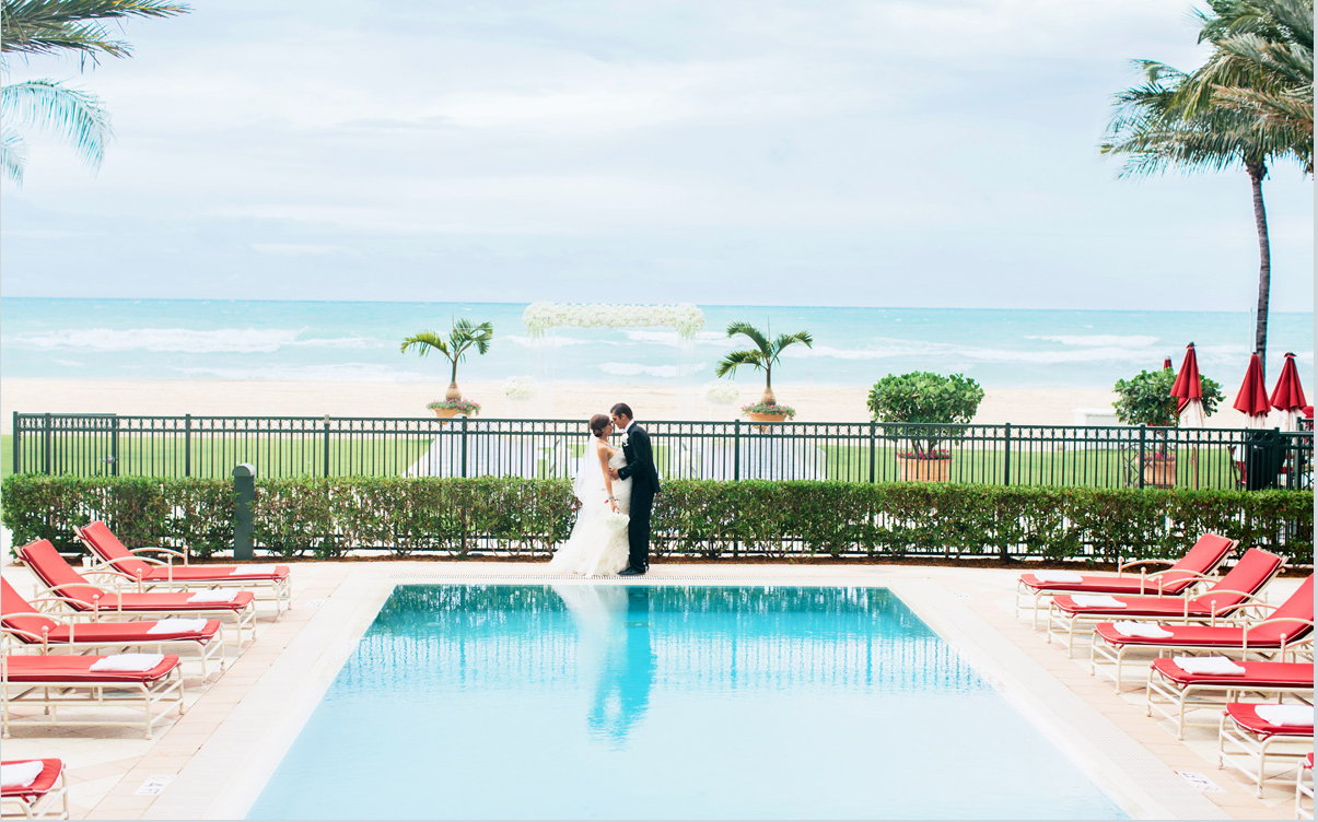 Wedding couple standing poolside at Acqualina Resort & Spa on the Beach