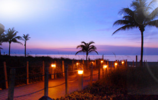 Beach access lit up with lights early in the morning as the sun rises in the pink sky.