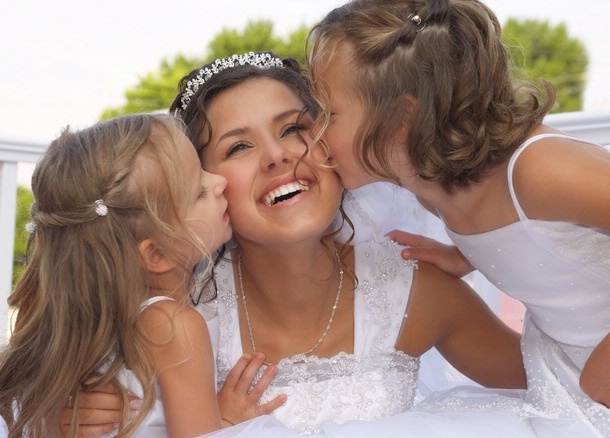 Two young girls kissing bride on the cheeks