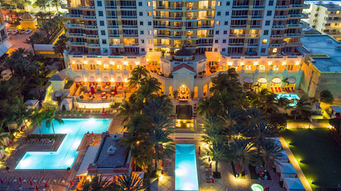 View of beautiful Acqualina grounds with brightly lit pools and rooms at nighttime.