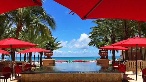 Red umbrellas and infinity pool at Acqualina Resort & Spa