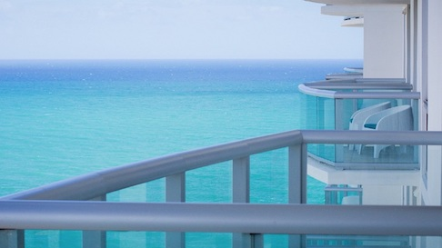 Balcony overlooking bright blue ocean waters.