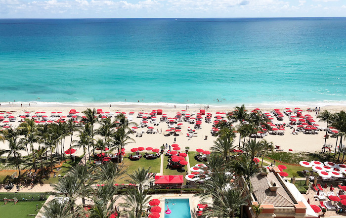 Aerial view of Acqualina Resort & Spa lawn and beach area with red lounge chairs and lawn decoration