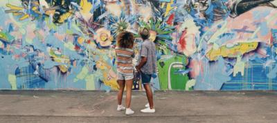 Couple looking at graffiti art in Miami.