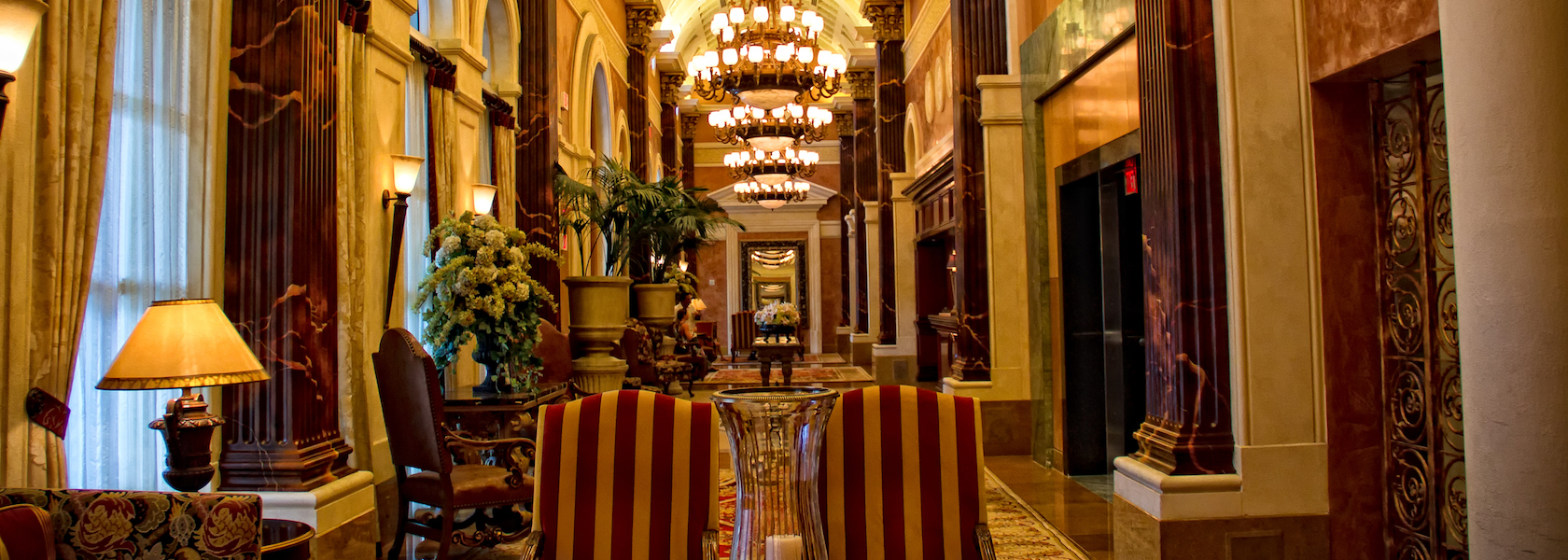 Opulent gold and red lobby with chandeliers at Acqualina Resort & Spa