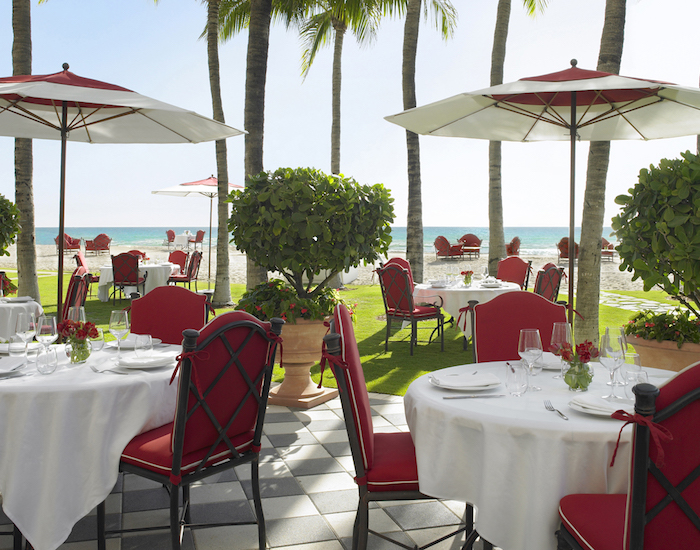 Outdoor dining area with red chairs and umbrellas next to grassy lawn and the ocean and beach. Costa Grill at Acqualina Resort