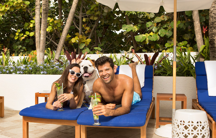 Young couple laying on lounge chairs enjoying beverages