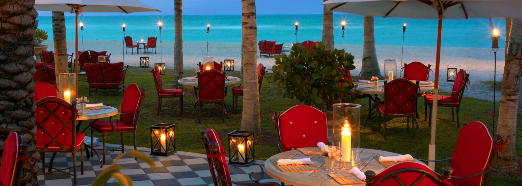 Evening with tiki torches around the outdoor dining area next to the turquoise ocean