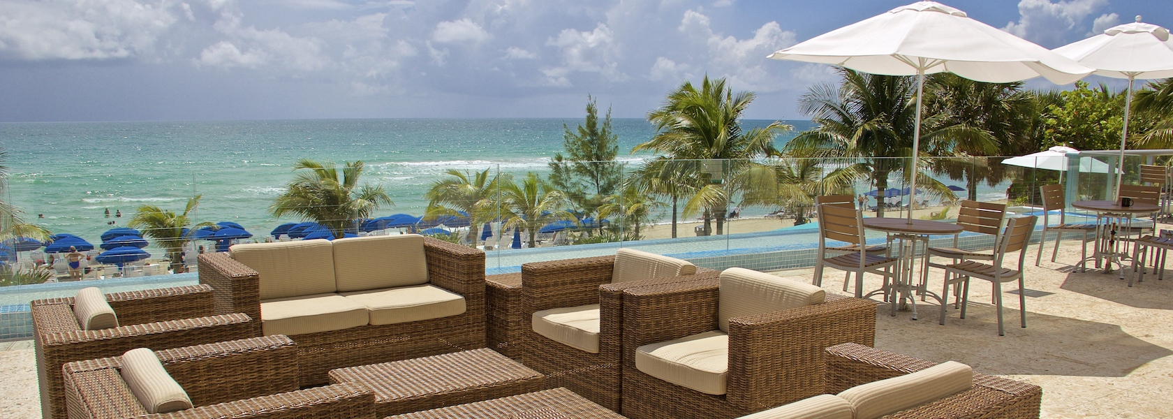 Lounge chair by pool overlooking ocean at Marenas Beach Resort