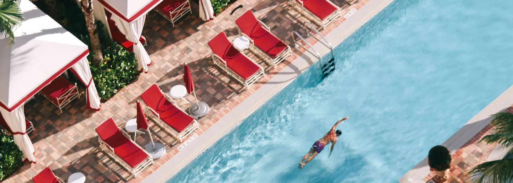 Man swimming in lap pool next to red lounge chairs at Acqualina Resort & Spa