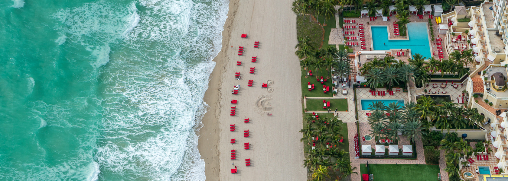 Aerial view looking directly down at turquoise oceans, red lounge chairs and Acqualina lawn.