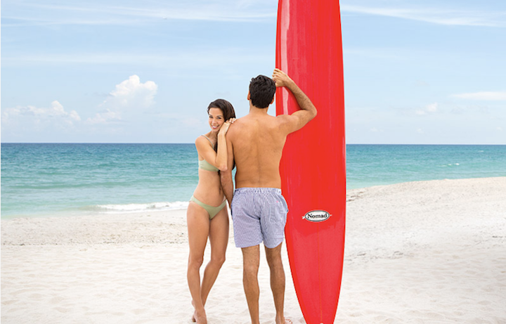 Young couple standing on the beach with surfboard
