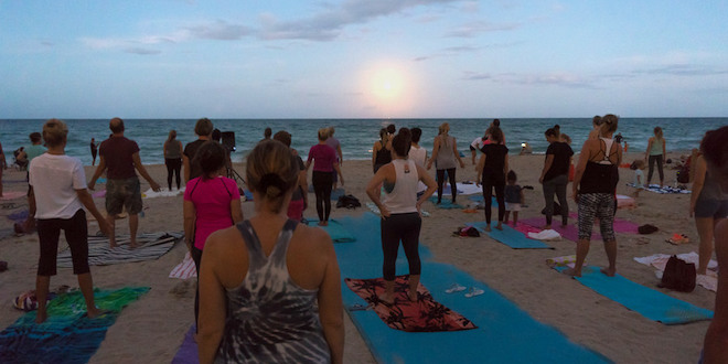 Yoga participants standing facing the ocean as the moon rises over the ocean.