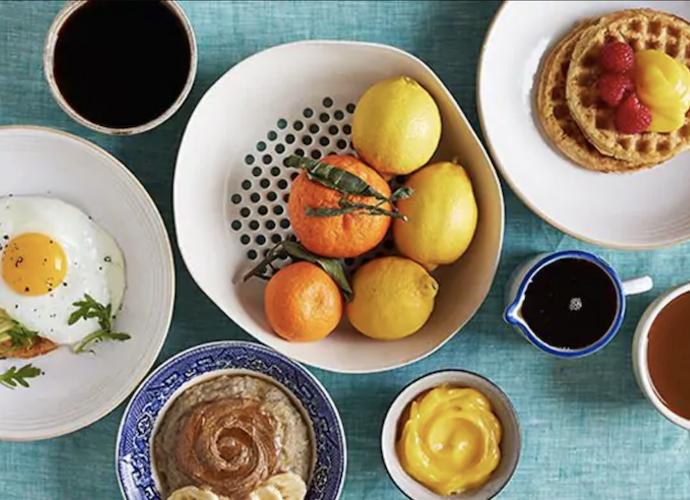 Breakfast spread - eggs, fruit, rolls, coffee, waffles.