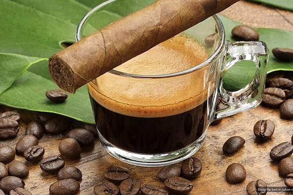 Cigar sitting on top of glass of cuban coffee surrounded by coffee beans