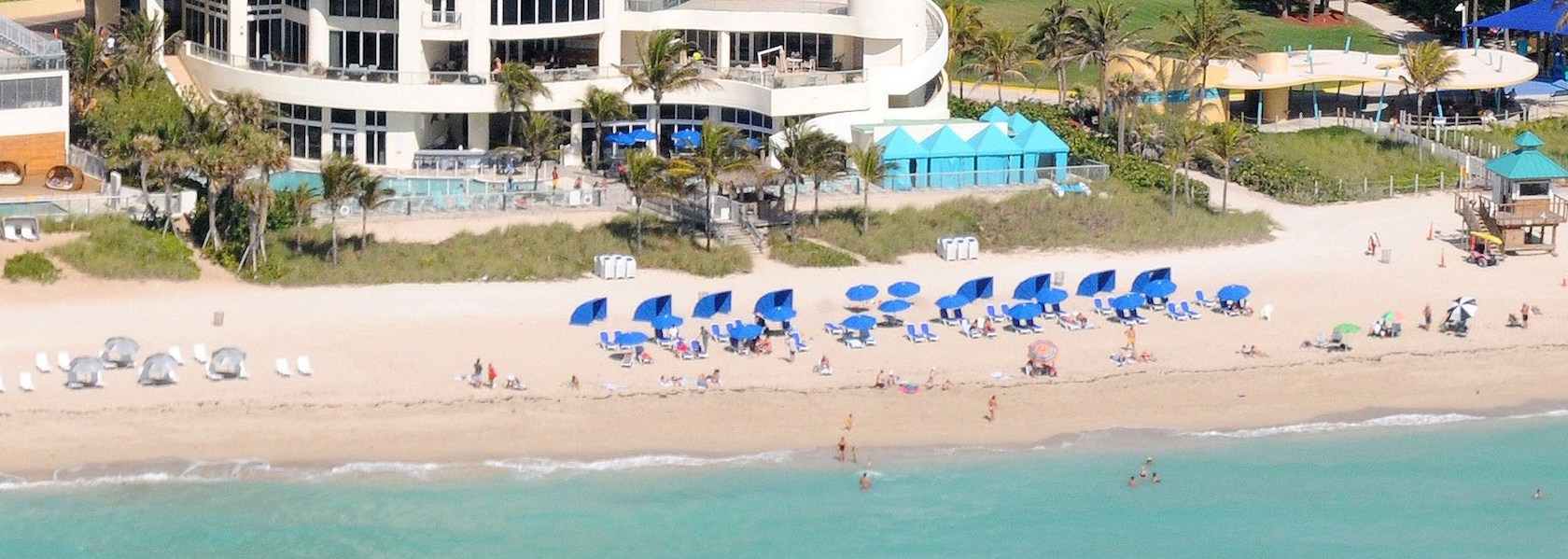 View of the Doubletree Ocean Point Resort with blue umbrellas and lounge chairs on the beach next to the ocean.