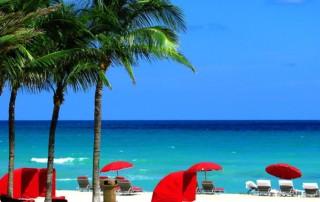 Red cabanas on white sandy beach next to palm trees.