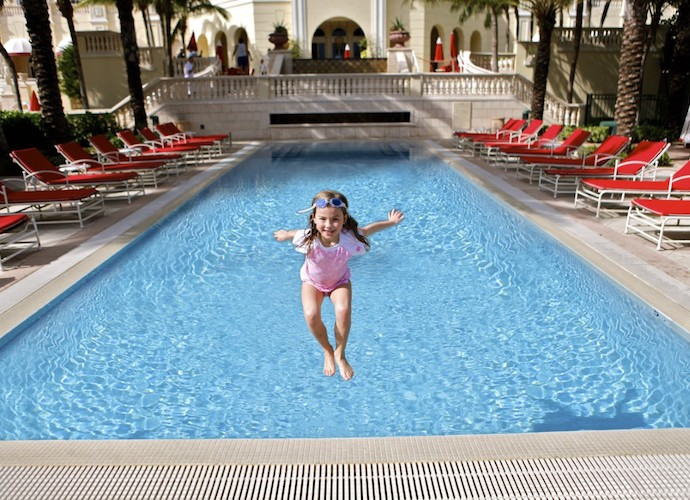 Young girl jumping into pool