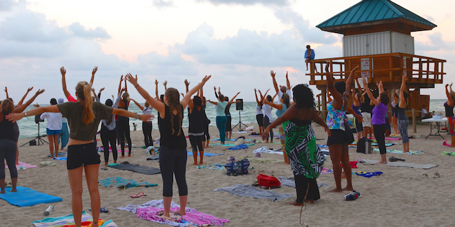 People standing on yoga mats on the beach during full moon yoga.