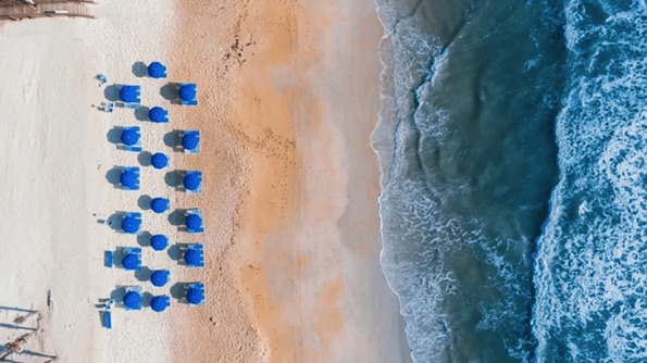 Aerial view of beach and beach chairs by ocean.