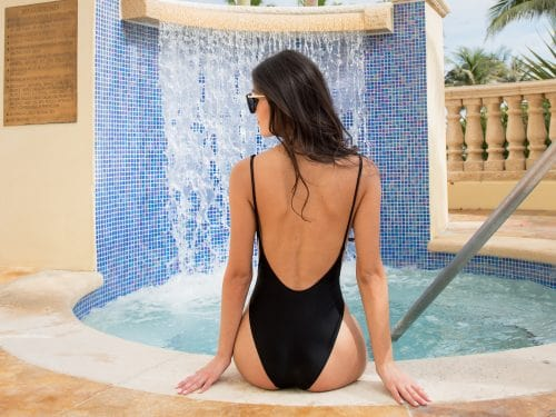 Woman sitting in swimsuit at Acqualina pool