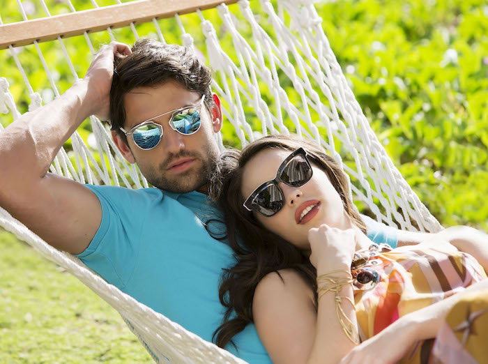 Young couple laying in a hammock in the sun